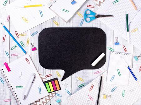 Empty black Bubble chalkboard on wooden background. Table with notebooks, pens, paper clips