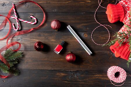 Red nail polish on wooden Christmas background