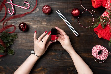The woman paints nails in red color. Wooden Christmas background 写真素材 - 131690015