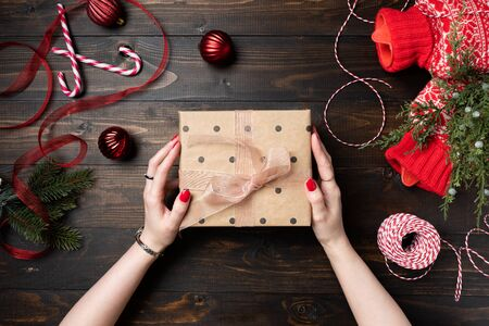 Woman hand with red nails holding Christmas presents on a wooden table background 写真素材