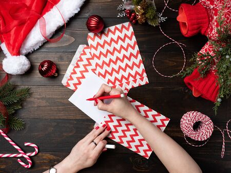 Woman hand with red nails holding Christmas letter on a wooden table background. Top view on Santa hat. New Year, preparation for holiday concept