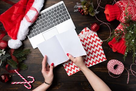 Woman hand with red nails holding Christmas letter on a wooden table background