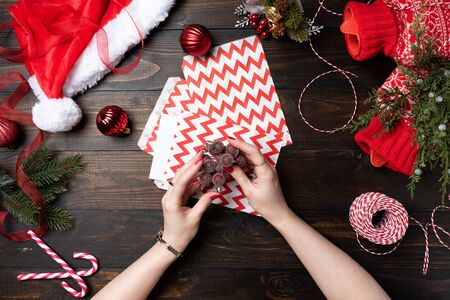 Woman hand with red nails holding Christmas winter berries on a wooden table background. Top view on Santa hat. New Year, preparation for holiday concept 写真素材