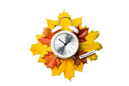 Alarm clock on yellow and red foliage isolated on white background. Time change concept, october