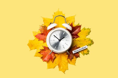 Alarm clock on red foliage isolated on yellow background. Time change concept