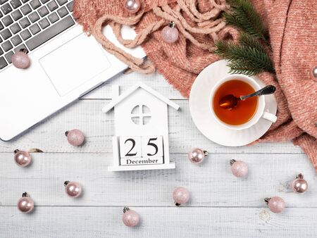 Workspace with pink Christmas tree ornaments, laptop, cup of tea. Top view of cozy office wooden desk. Christmas background, flat lay.