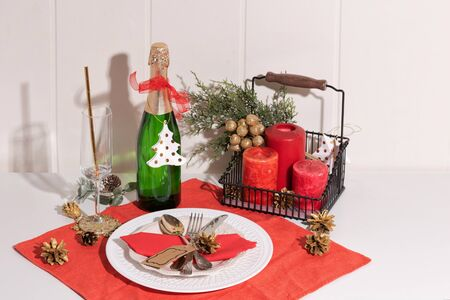 Christmas table setting. Red decoration with Santa hat and fir-tree branch. Flat lay, top view