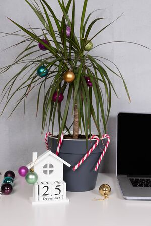Christmas palm tree with ornaments. Office desk laptop with decoration, grey wall, white table. 25 December on the calendar