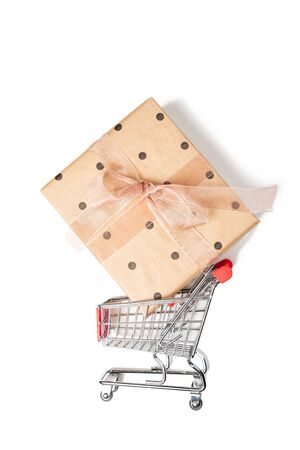 Shopping cart with gift boxes, flat lay. Christmas and sale concept on white background 写真素材