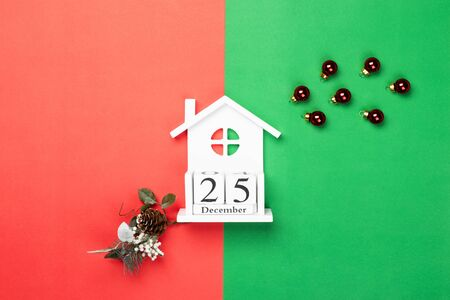 Wooden cubes calendar 25 December on red and green paper background. Christmas decorations. Flat lay, top view.