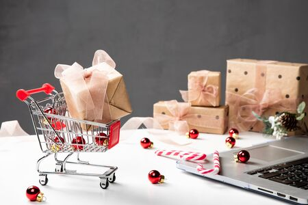Christmas shopping cart, small gift boxes, laptop on the desk. Online shopping concept.
