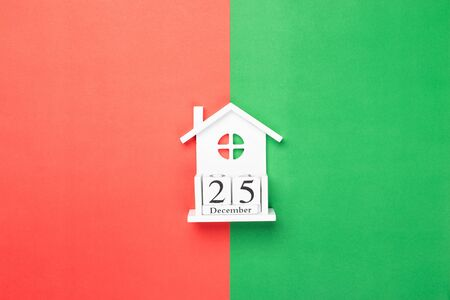 Wooden cubes calendar 25 December on red and green paper background 写真素材