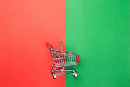 A shopping cart on red and green paper background. Christmas candy canes. Flat lay, top view.