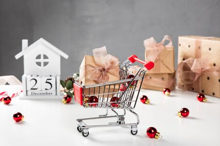 Christmas shopping cart, small gift boxes, laptop on the desk. 25 December on the wooden calendar. Online shopping concept.