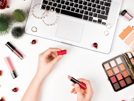 Workspace with laptop, cosmetics and Christmas decorations. Red baubles. lipstics, jewelry, Eyeshadow Palette