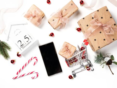 Christmas online shopping. Woman hand holding phone. White table with gift boxes and small shopping cart. 25 December on the wooden calendar. Flat lay, top view.