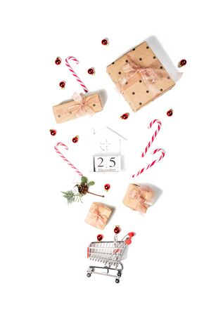 Shopping cart with gift boxes, flat lay. Christmas and sale concept. 25 December on the wooden cube calendar 写真素材