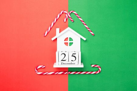 Wooden cubes calendar 25 December on red and green paper background. Christmas candy canes. Flat lay, top view.