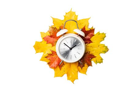 Alarm clock on yellow and red foliage isolated on white background. Time change concept