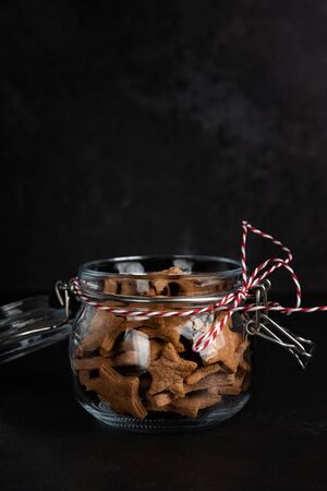 Glass Jar with homemade star-shaped gingerbread cookies on a dark 写真素材