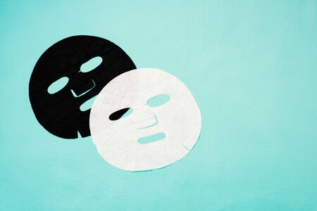 Black and white facial sheet masks on a blue background Stock fotó