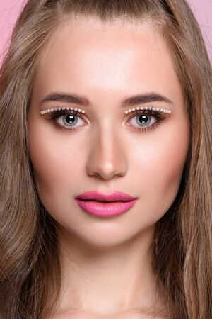 Beautiful girl with pearls make-up, pink lips.