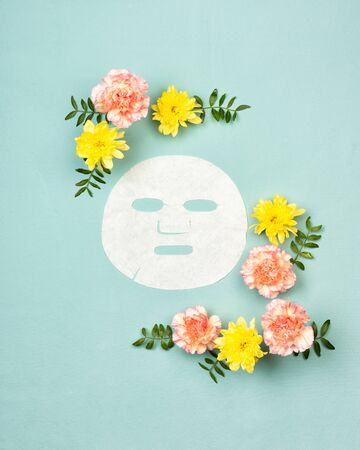 White facial sheet mask for skin face, pink and yellow flowers on a turquoise