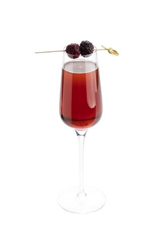 Kir royale alcoholic classic cocktail in a champagne glass isolated on white background. Red drink with blackberry