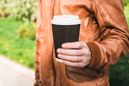 Male hand holding a coffee paper cup. Man in brown leather jacket holds drink on the street. Summer sun, green grass Stock Photo