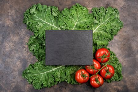 Kale salad leaf and red tomatoes with water drops on an old rustic metal tray. Green nature background. Black stone chalk board for copy space