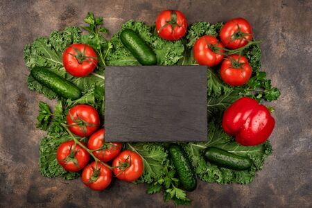 Kale salad leaf and red tomatoes, pepper, cucumbers, avocado with water drops on an old rustic metal tray. Green nature background. Black stone chalk board for copy space