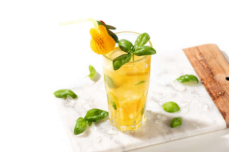 Citrus lemonade or mojito cocktail with lemon and orange and basil. Cold beverage or drink with ice on marble cutting board Stock fotó