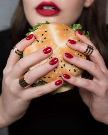 Glamor woman with a perfect fashion red manicure and makeup eating burger. Fast food concept