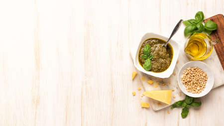 Bowl with pesto and fresh basil, garlic, parmesan cheese, pine nuts and olive oil on marble board. Kitchen wooden table with Italian sauce