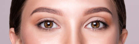Female brown eyes with light makeup. Cosmetics and Beauty concept. Close up shoot, macro