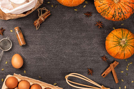 Baking ingredients for pumpkin pie or cookies. Cinnamon, flour, eggs, whisk, rolling pin on dark wooden table Frame for recipes notebook.
