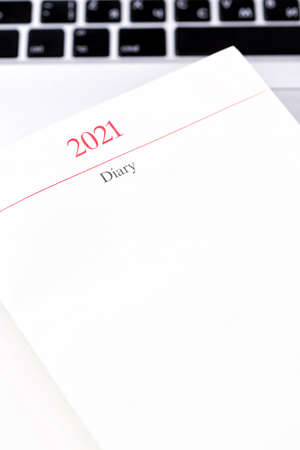 Red diary planner with 2021 year calendar and laptop