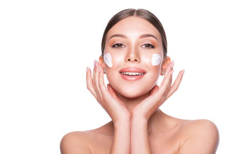 Beautiful model woman with moistening cream on face.