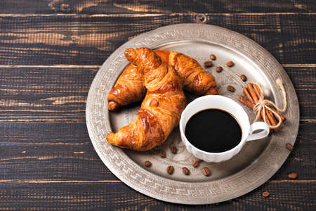 Croissant with chocolate hazelnut spread and cup of coffee