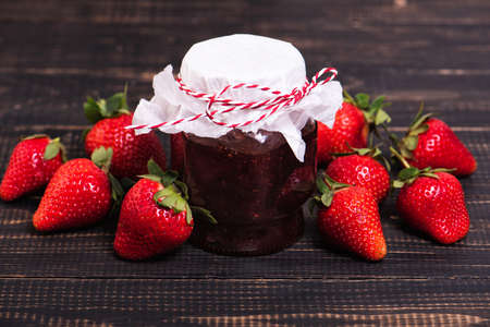 Jar of strawberry jam on wooden rustic board.