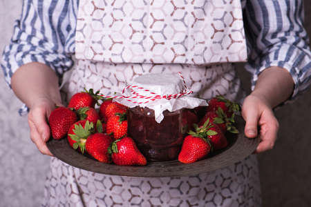 Woman holds a metal copper tray with a jar of strawberry jam