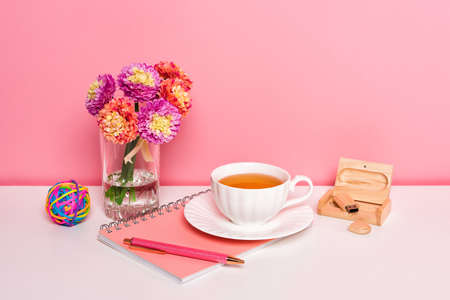 Home office workspace with a flowers cup of tea on white table Standard-Bild