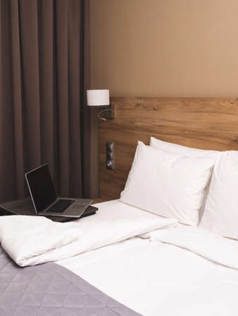 Modern hotel room with king-size bed and laptop