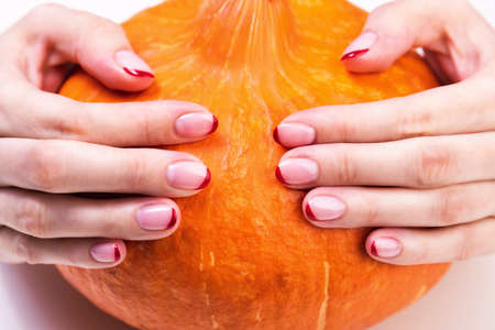Female hands with a trendy autumn french manicure with red tips