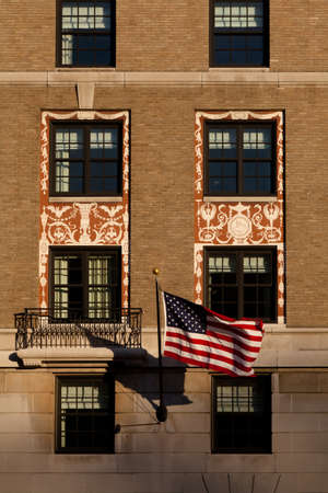 Detail of a building with windows and an American flag