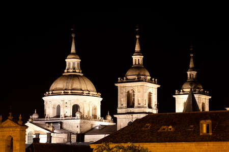 San Lorenzo de El Escorial Monastery  at night beautifully illuminated. Four towers are set off by black background. 新聞圖片