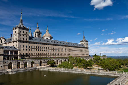 San Lorenzo de El Escorial Monastery with a reflecting pool with floating swan. The towers of the church and monastery are set of by a bright blue sky with a few white clouds.