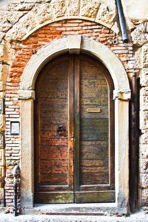 Oude houten deur met een metalen klopper en brief slot - prachtige textuur. De deur heeft weinig metalen studs. Aan de zijkant is er een modern deurbel en intercom. Bakstenen en leidingen en een stenen boog maken het plaatje compleet.
