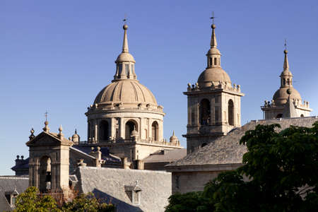 San Lorenzo de El Escorial Monastery - towers of the church and monastery are set of by a bright blue sky.
