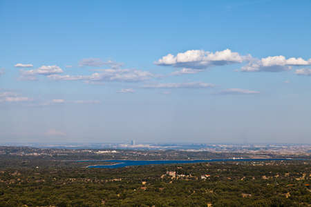 View of the city of Madrid from a distance. Bright blue lake in the foreground. Taken on a sunny day with bright blue sky and a few white clouds.